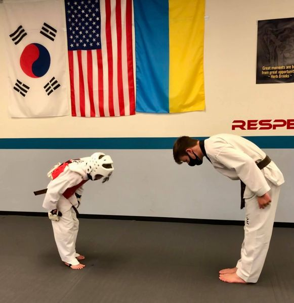 Martial Arts student in sparring gear and Instructor Joseph Teger bow to one another in front of flags