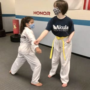 Photo of two girls practicing self-defense moves in their Taekwondo Class