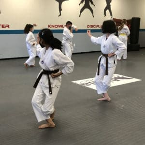 Photo of 2 girls standing in the final position of their poomsae (Taekwondo form)