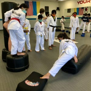photo of a girl on a kicking bag stretching her leg to reach the next step of an obstacle course in her martial arts class